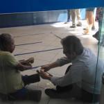 Bom Exemplo: Gerente da Caixa se senta no chão para atender homem deficiente.